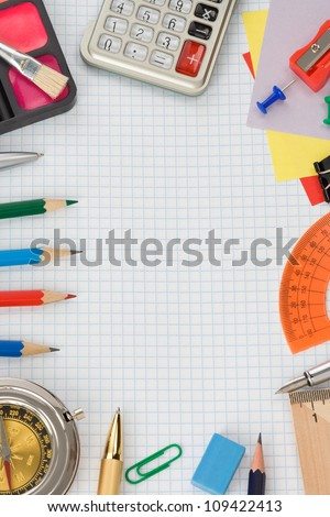 school supplies on  checked notebook paper - stock photo