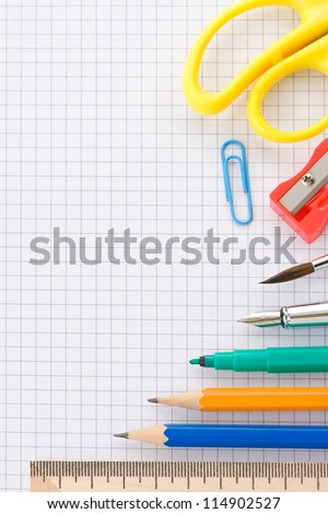school supplies on checked paper notepad background - stock photo