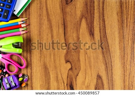 School supplies side border on a wooden desk background - stock photo