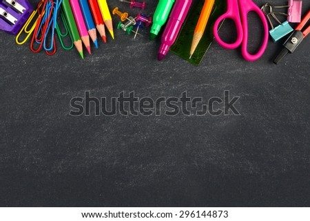 School supplies top border on a chalkboard background - stock photo