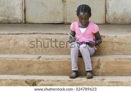 School Symbol: Beautiful black African teenage girl writing her lessons down in a school environment in the public school of Bamako, Mali.  - stock photo