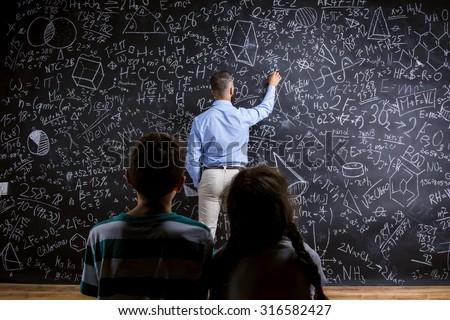 School teacher in front of big blackboard and his students - stock photo