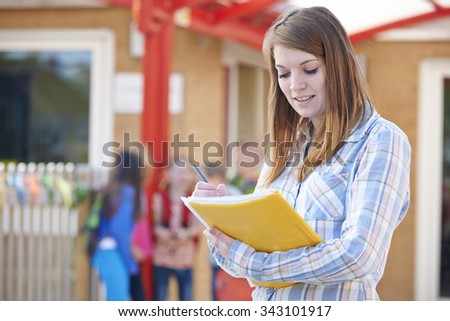 School Teacher Making Notes In Playground - stock photo