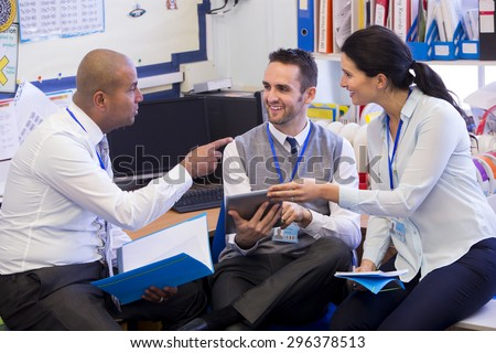 School teachers gather in a small school office for a chat. They look happy. A woman and two men group together. A man holds a digital tablet - stock photo