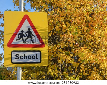 School warning sign on the yellow background of autumn leaves. - stock photo