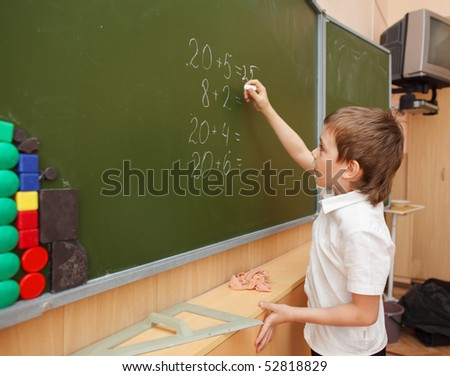 Schoolboy about a board solves examples - stock photo