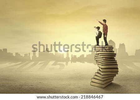 Schoolboy and his teacher looking at the sky using binoculars - stock photo