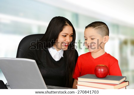 Schoolboy and teacher looking at laptop and talking - stock photo