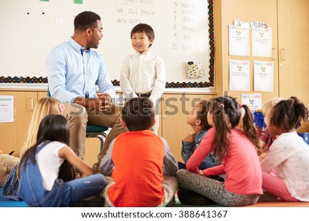 Schoolboy at front of elementary class with teacher - stock photo