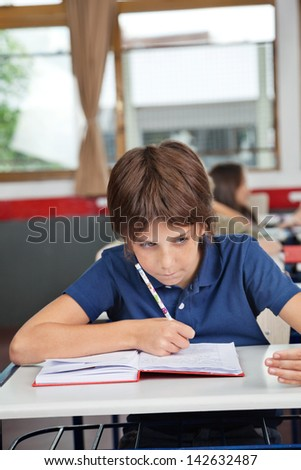 Schoolboy cheating at desk during examination in classroom - stock photo