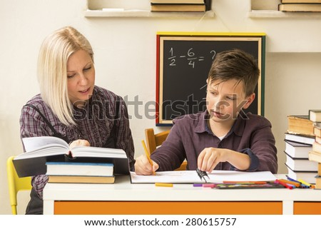 Schoolboy do homework at home with a tutor. - stock photo