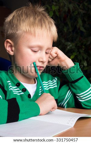 Schoolboy doing his difficult school homework with problems - stock photo