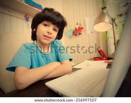 schoolboy doing homework on a laptop. instagram image retro style - stock photo