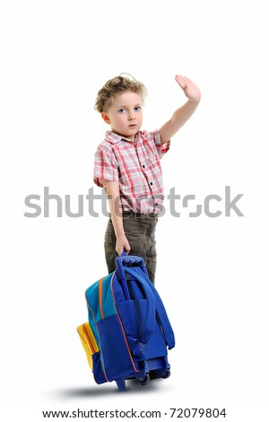 schoolboy holding his backpack and waving while going to school - stock photo