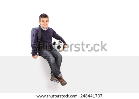 Schoolboy holding soccer ball seated on a panel isolated on white background - stock photo