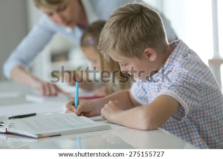 Schoolboy in classroom writing on notebook - stock photo