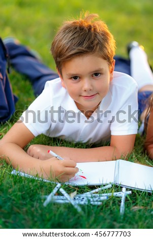schoolboy in the park draws - stock photo