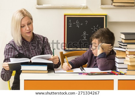 Schoolboy is learning with the teacher. - stock photo