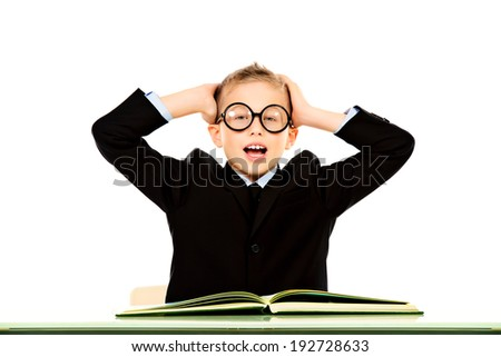 Schoolboy is sitting at table on white background - stock photo