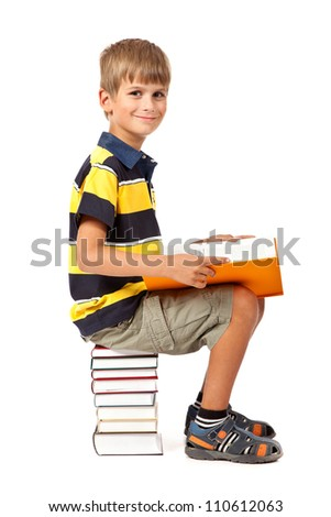Schoolboy is sitting on books isolated on a white background. Back to school - stock photo