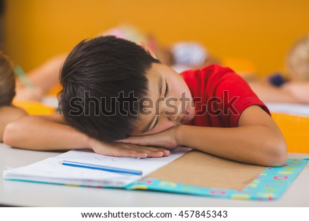 Schoolboy lying on desk in classroom at school - stock photo
