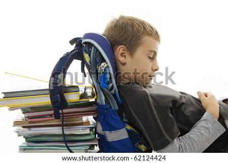Schoolboy lying on floor, sleeping on school bag and books. Isolated on white - stock photo