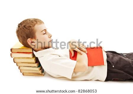 Schoolboy lying on floor, sleeping on school books. Isolated on white - stock photo