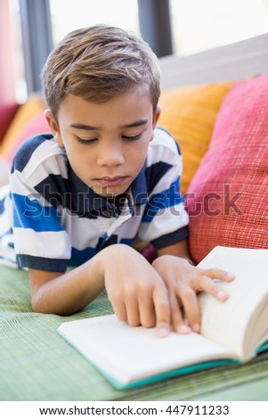 Schoolboy lying on sofa and reading book in library - stock photo