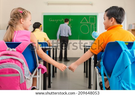 Schoolboy passing a love note or cheat sheet to his classmate in classroom, rear view - stock photo