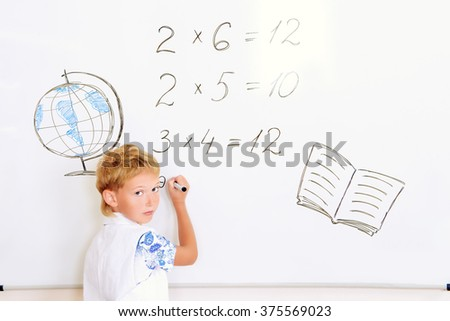 Schoolboy performs the tasks at the blackboard in the classroom. Education. - stock photo
