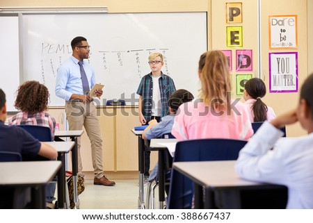 Schoolboy presenting to his elementary school classmates - stock photo