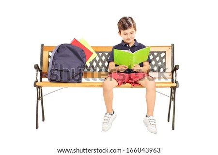 Schoolboy seated on a wooden bench reading a book isolated on white background - stock photo