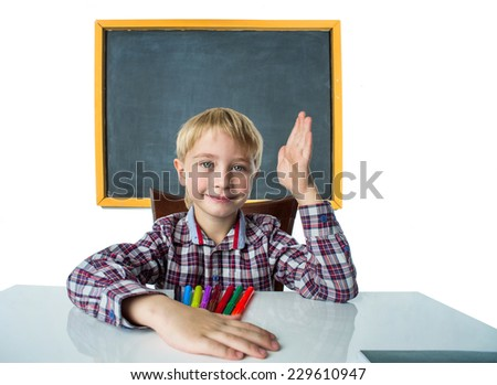 Schoolboy sits at his desk with his hand raised - stock photo