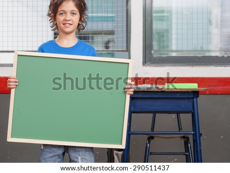 Schoolboy standing holding empty chalkboard. - stock photo