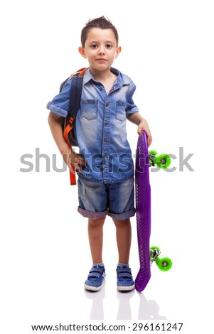 Schoolboy standing with a skateboard and backpack on white background - stock photo