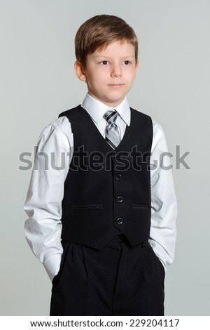 Schoolboy standing with his hands in his pockets - stock photo