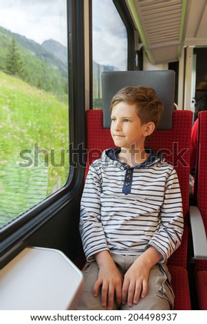 schoolboy travels by train at the window - stock photo