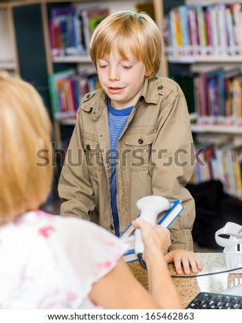Schoolboy waiting while librarian scanning book at checkout counter in library - stock photo
