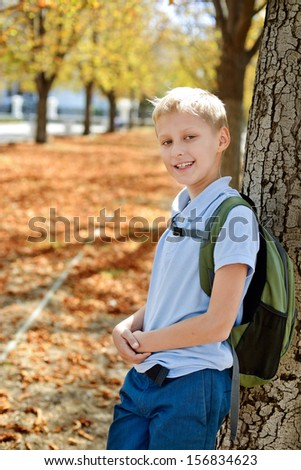 schoolboy with backpack after school in park - stock photo