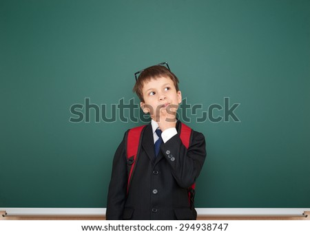 Schoolboy with backpack on school board background - stock photo