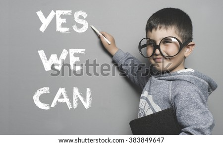 schoolboy with goggles and funny gesture writing on the blackboard the text yes we can - stock photo