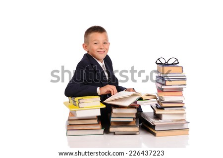 Schoolboy with huge stack of books isolated over white background - stock photo