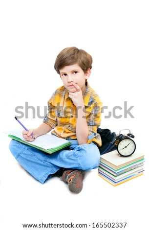 schoolboy with notebook on his knees and a stack of books - stock photo