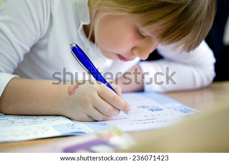 schoolboy writes in a notebook at school - stock photo