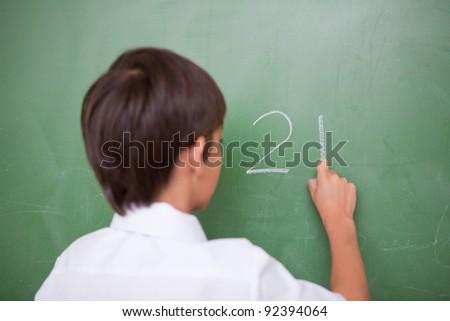 Schoolboy writing an addition on a blackboard - stock photo