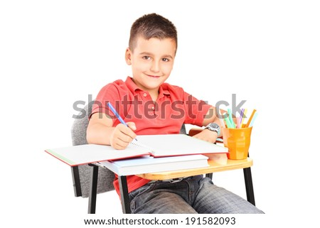 Schoolboy writing in a notebook seated on a school desk isolated on white background - stock photo