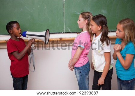 Schoolboy yelling through a megaphone to his classmates in a classroom - stock photo