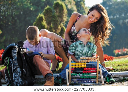 schoolboys studying and smiling in park with their mother. - stock photo