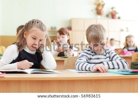 Schoolchild behind desks at school - stock photo