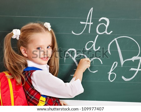Schoolchild writting on blackboard in schoolroom. - stock photo